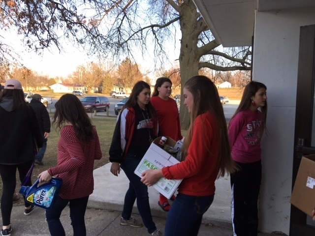 Student Council members helping families load donations.